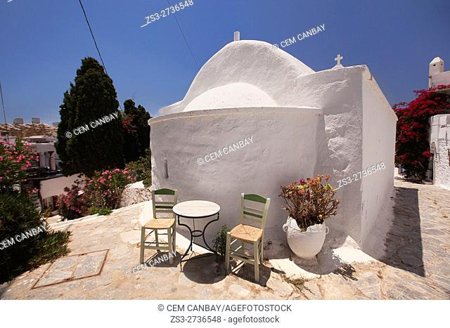 Tables and chairs of a restaurant in front of a whitewashed chapel in the old town Chora, Amorgos, Cyclades Islands, Greek Islands, Greece, Europe