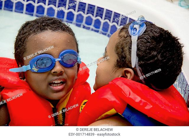 Two brothers playing in the pool