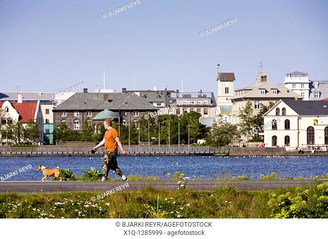 Man walking his dog by Tjornin lake  Reykjavik Iceland