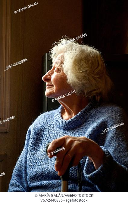 Portrait of old woman at home, smiling and looking at the window. Low key