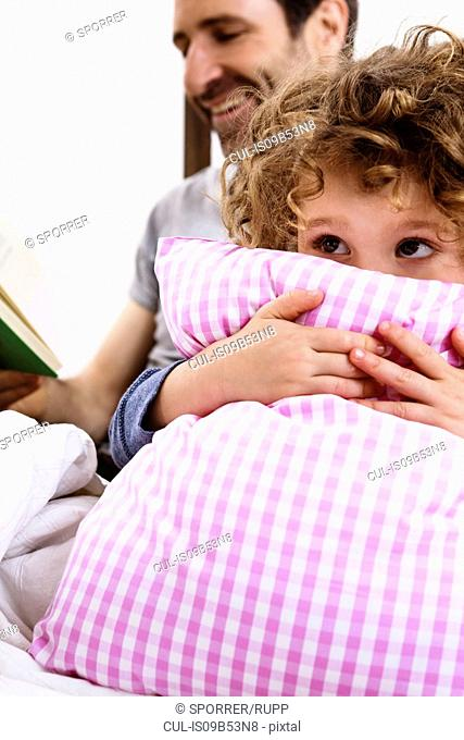 Girl hugging pillow while father reads storybook in bed
