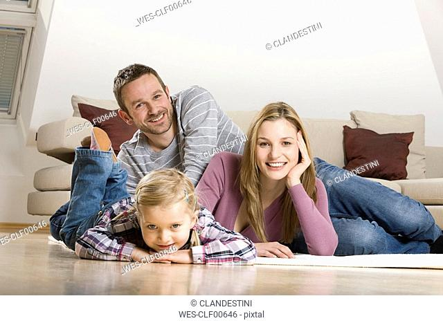 Parents and daughter 3-4, relaxing at home