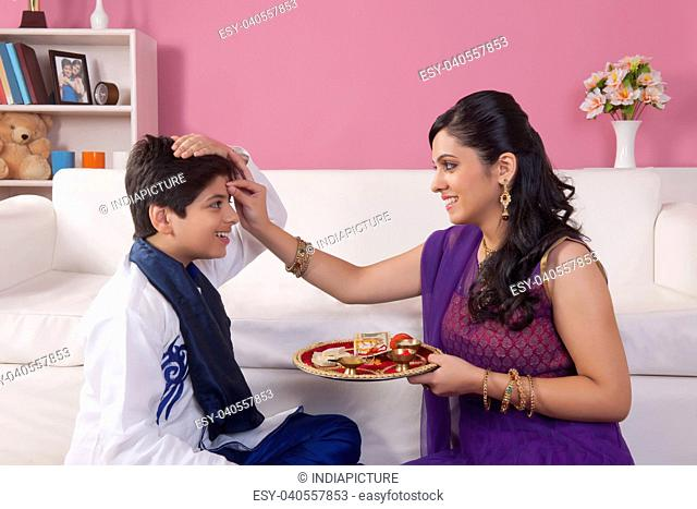 Sister applying tilak to her brother at Raksha Bandhan