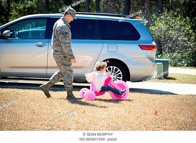 Male soldier playing with daughter on pink tricycle at air force military base