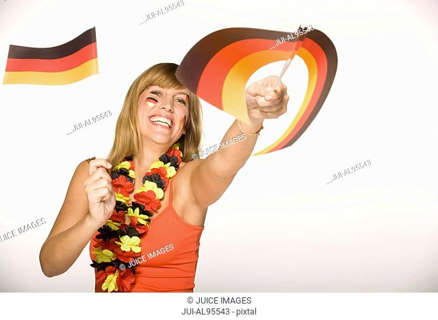 Young woman waving German flags