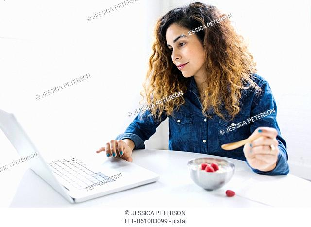 Woman using laptop and eating yoghurt