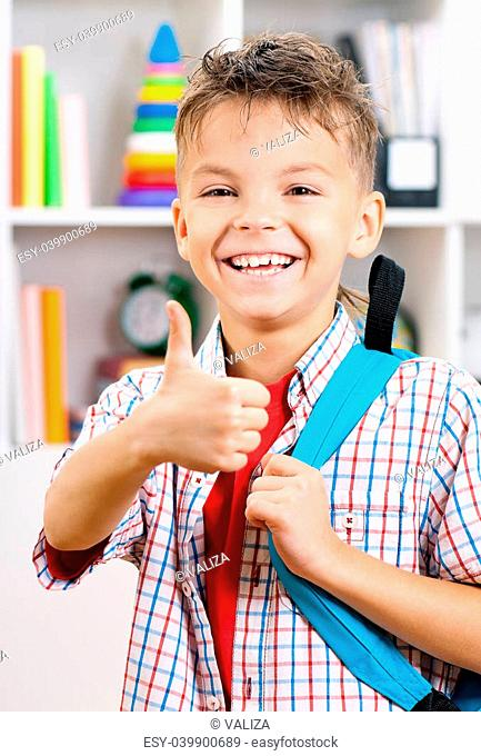Happy schoolboy with backpack showing thumbs up sign