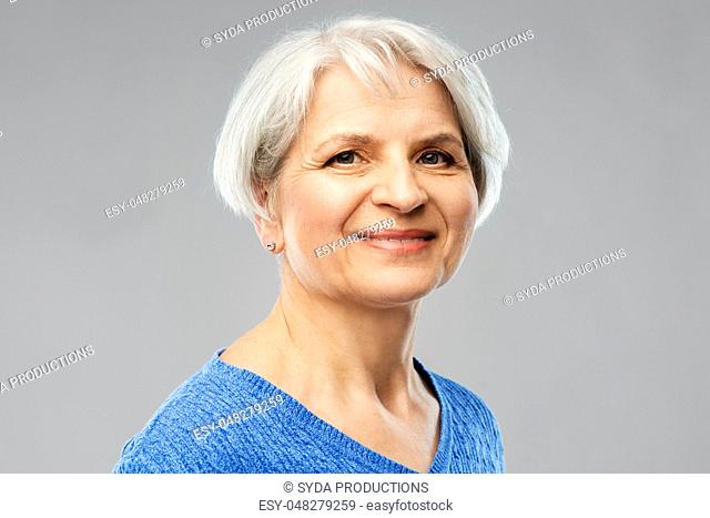 portrait of smiling senior woman in blue sweater