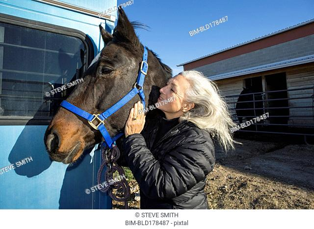 Caucasian woman petting horse on ranch