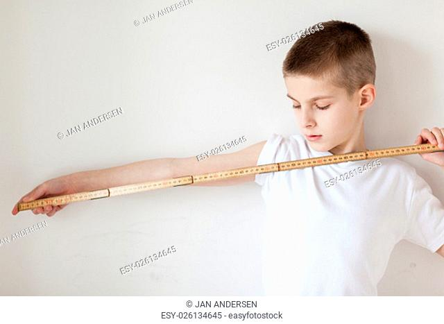 Half Body Shot of a Handsome Young Boy Holding a Meter Stick with One Arm is Stretching Against Plain White Wall Background