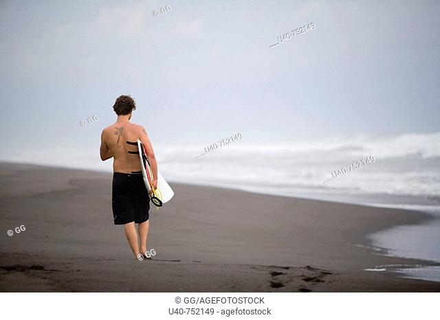 Guatemala, Paredon beach, man with surfboard