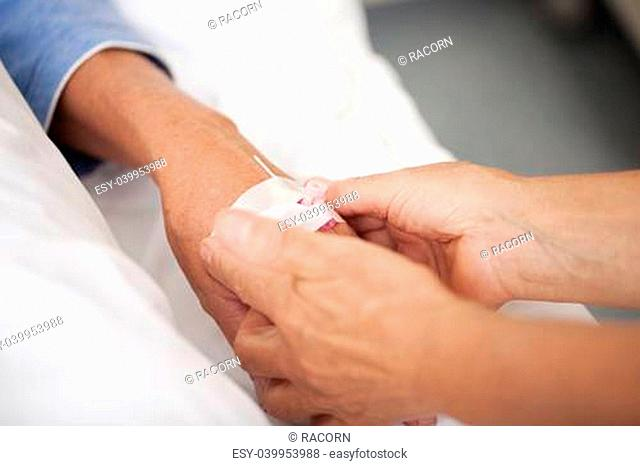 Closeup of female nurse adjusting drip on patients hand in hospital