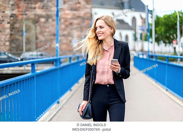 Smiling businesswoman walking on a bridge looking at her smartphone