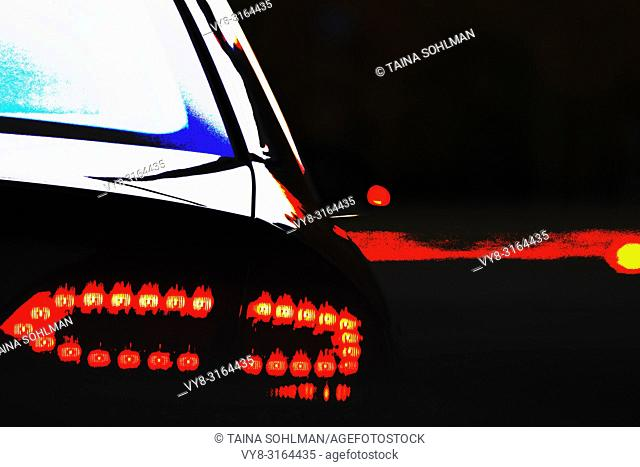 Car rear light in intersection signaling right turn. Photograph with filters