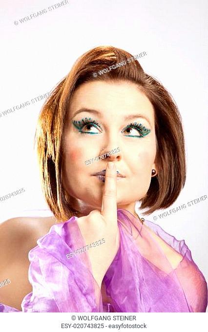Frau mit Zeigefinger am Mund blickt nachdenklich nach oben