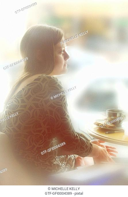 Profile of Beautiful Woman Gazingat Coffee Shop