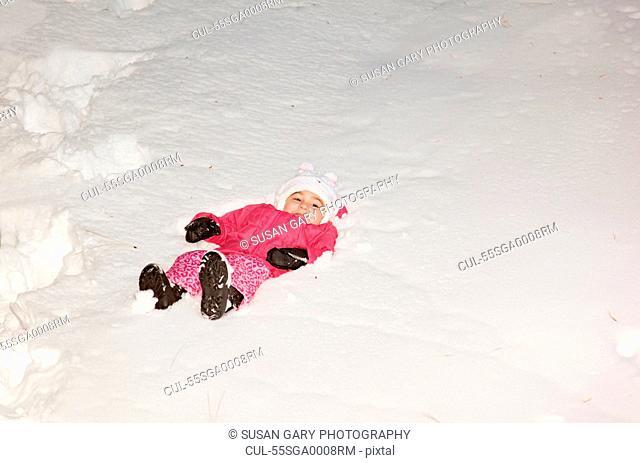 Girl lying in deep snow