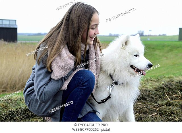 Smiling girl crouching on a meadow besides her dog