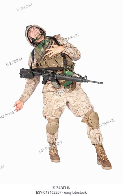 Studio shoot of army soldier in combat uniform and body armor, screaming, clutching chest, dropping weapons and falling down after being fatally shot in...