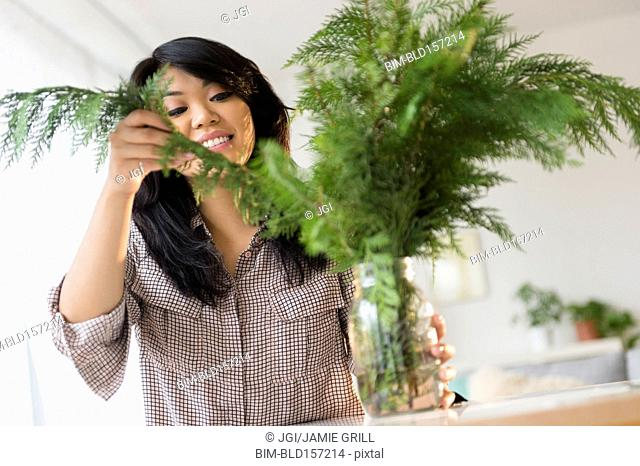 Pacific Islander arranging plants in jar