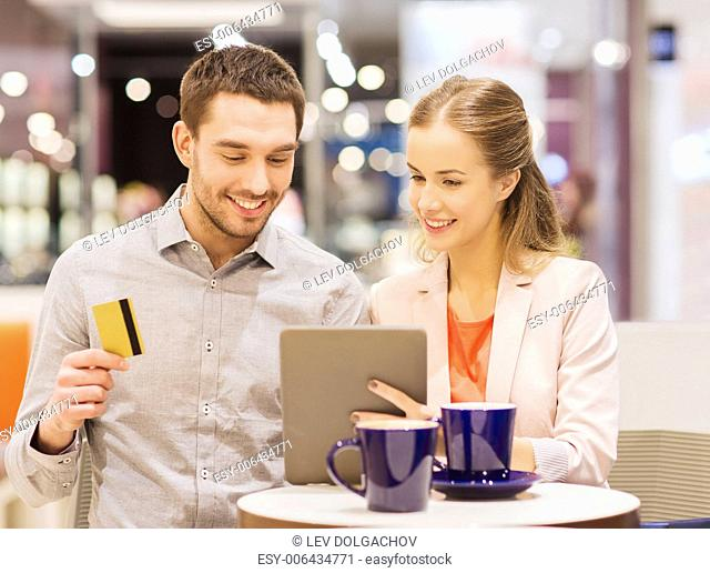 sale, shopping, consumerism, leisure and people concept - happy couple with tablet pc and credit card drinking coffee in mall