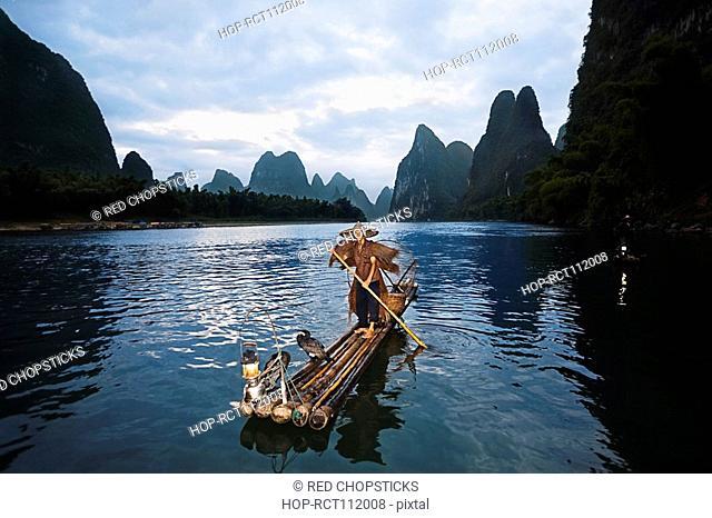 Fisherman standing on a wooden raft in a river, Li River, XingPing, Yangshuo, Guangxi Province, China
