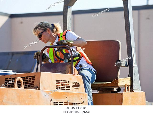 Woman driving stream roller repairing pot holes in parking lot; Edmonton, Alberta, Canada