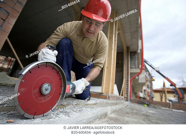 Construction worker cutting concrete block with electroportable machine with diamond disc. Building houses