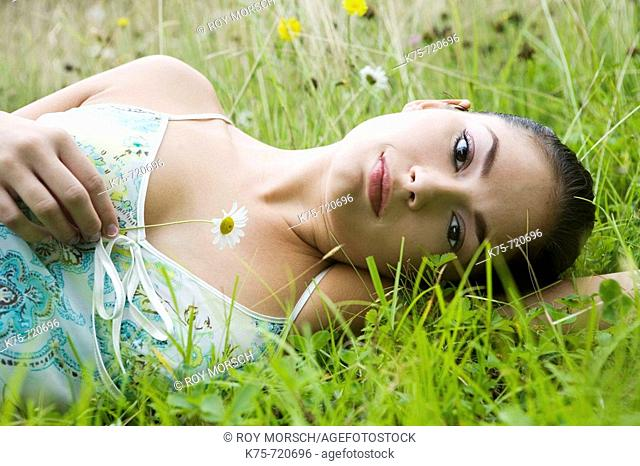 Young woman lying in field of wildflowers