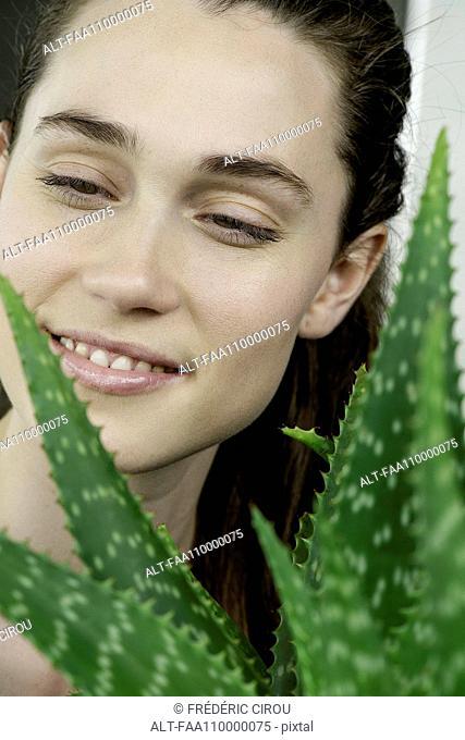 Young woman looking at aloe vera plant