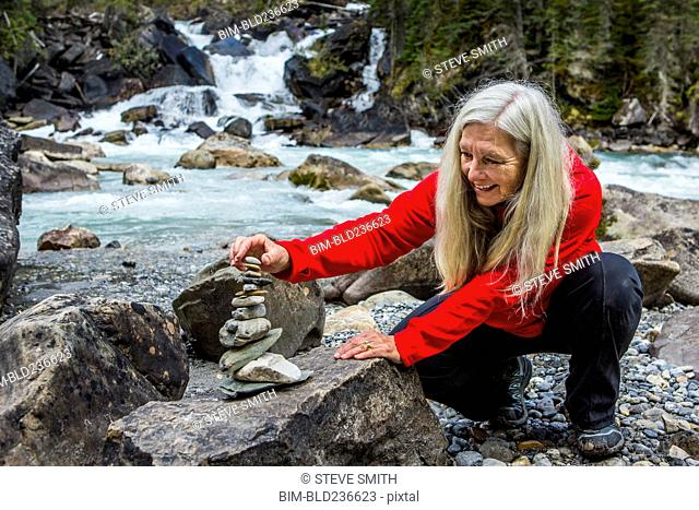 Caucasian woman balancing stack of rocks