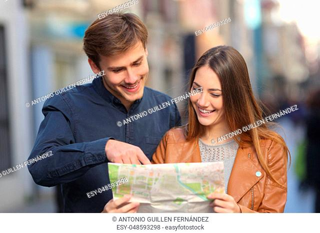 Front view portrait of a happy couple of tourists on vacation using a paper map in the street