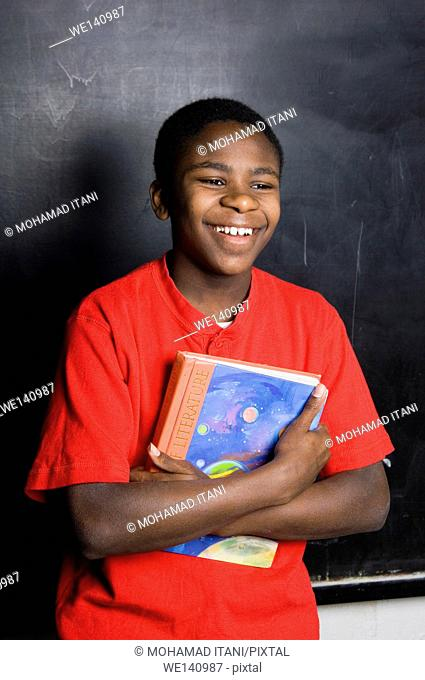 Student In Classroom laughing while holding a book