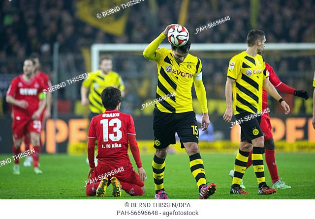 Dortmund's Mats Hummels (C) and Cologne's Yuya Osako react during the Bundesliga soccer match Borussia Dortmund vs 1st FC Koeln in Dortmund, Germany