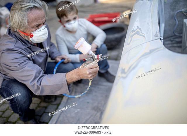 Senior man spraying on car with boy watching him