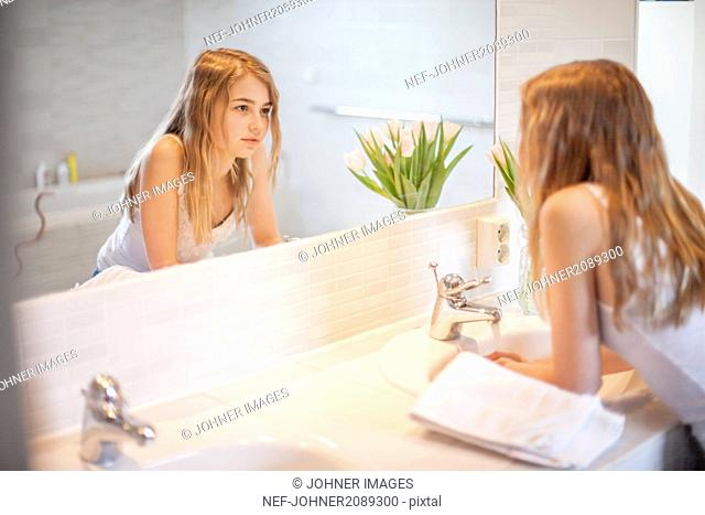 Girl in bathroom looking at mirror