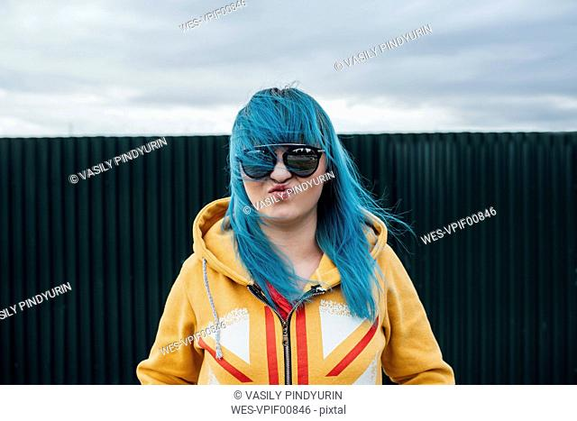 Portrait of young woman with dyed blue hair wearing sunglasses and hooded jacket