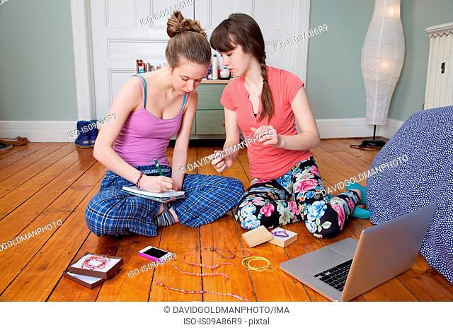Girls sitting on bedroom floor with laptop, making friendship bracelets