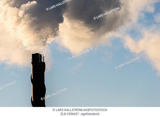 Smokestack emitting white smoke into blue sky, Stockholm, Sweden