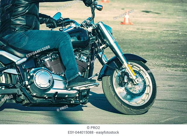 Biker in jeans riding a motorcycle. Side view. Soft focus