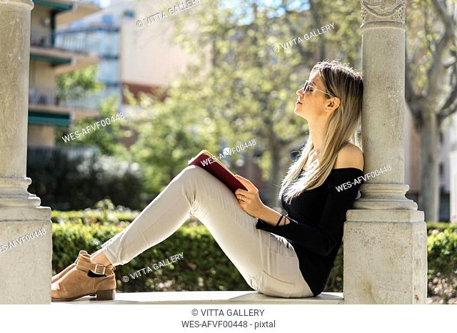 Young woman with notebook relaxing on bench
