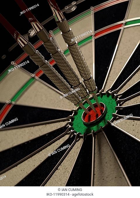 Three darts hitting bull's eye on dartboard