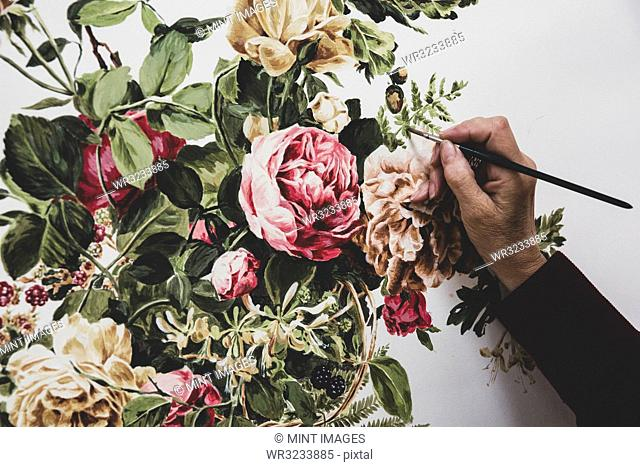 Close up of artist working on painting of pink tea roses, leaves, berries and other flowers