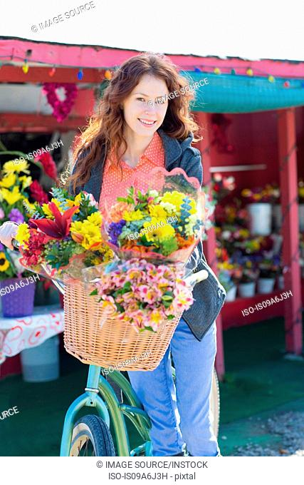 Woman carrying flowers in bicycle basket