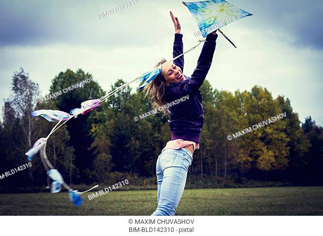 Woman flying kite in field