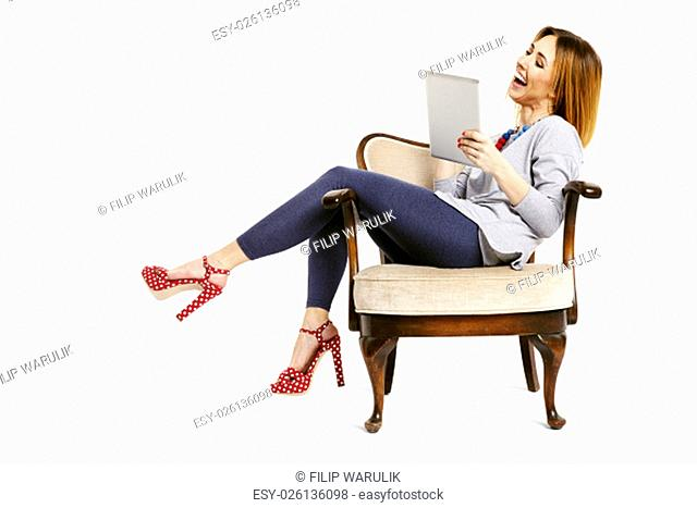 Young woman sitting on a chair with pulled legs relaxing and watching good news e-mail on tablet