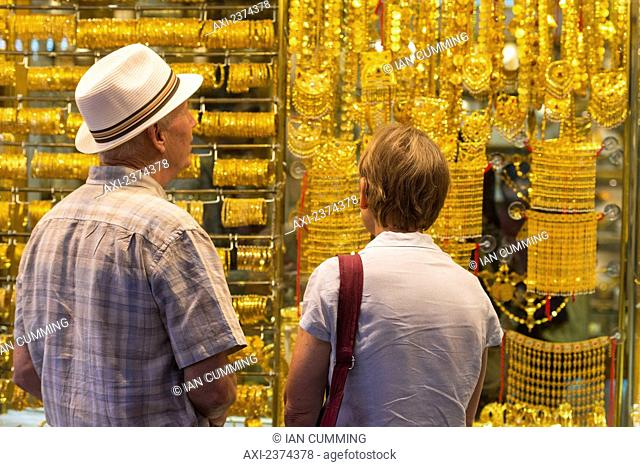 Western couple looking at gold jewellery for sale in window of shop in the gold souk; Dubai, United Arab Emirates