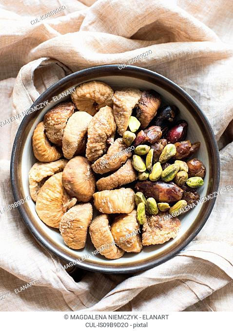 Dried fruit and mixed nuts in bowl, close-up