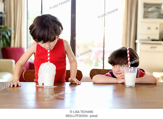 Little boy blowing bubbles in a glass of milk while his brother watching him
