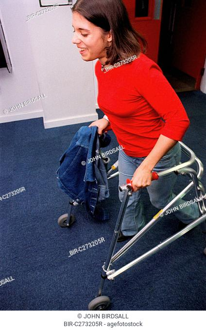 Teenage girl with physical disability using walking frame to walk along college corridor